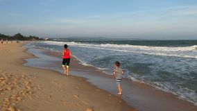 Γυναίκα με ένα παιδί που κατά μήκος seacoast απόθεμα βίντεο