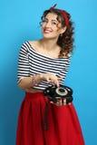 Γυναίκα με ένα παλαιό τηλέφωνο καλωδίων, που φορά ένα καρφίτσα-επάνω ύφος Στοκ Εικόνα