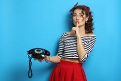 Γυναίκα με ένα παλαιό τηλέφωνο καλωδίων, που φορά ένα καρφίτσα-επάνω ύφος Στοκ Φωτογραφίες
