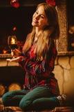 Γυναίκα με ένα ποτήρι του κρασιού από την εστία Νέο ελκυστικό wo στοκ εικόνες
