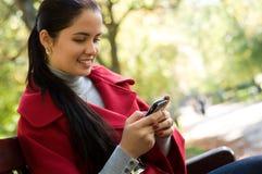 Γυναίκα με ένα τηλέφωνο κυττάρων, που κάθεται σε ένα πάρκο Στοκ Εικόνες