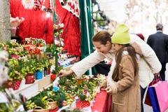 Γυναίκα με λίγη κόρη που αγοράζει τη floral σύνθεση στοκ εικόνα