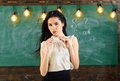 Γυναίκα με μακρυμάλλη στις άσπρες στάσεις μπλουζών στην τάξη Ο δάσκαλος με τα γυαλιά και την κυματίζοντας τρίχα φαίνεται προκλητι Στοκ εικόνες με δικαίωμα ελεύθερης χρήσης