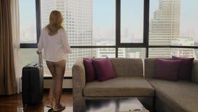 Γυναίκα με μια βαλίτσα στο υπόβαθρο των ουρανοξυστών σε ένα πανοραμικό παράθυρο στοκ φωτογραφίες