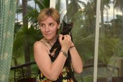 Γυναίκα με μια μαύρη γάτα στα χέρια της Στοκ εικόνα με δικαίωμα ελεύθερης χρήσης