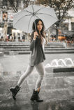 Γυναίκα με μια ομπρέλα κάτω από τη βροχή σε μια οδό πόλεων Στοκ Εικόνες