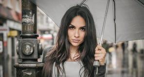 Γυναίκα με μια ομπρέλα κάτω από τη βροχή σε μια οδό πόλεων Στοκ Φωτογραφία