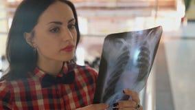 Γυναίκα με μια πεταλούδα που εξετάζει την των ακτίνων X εικόνα του θώρακα απόθεμα βίντεο