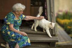 Γυναίκα με μια συνεδρίαση γατών στο μέρος του σπιτιού Στοκ Φωτογραφίες