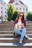 γυναίκα με μια συνεδρίαση φλυτζανιών limonade στα σκαλοπάτια και το κείμενο στο smartphone της Στοκ Εικόνες