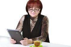 Γυναίκα με μια ταμπλέτα στον πίνακα σε ένα άσπρο υπόβαθρο Στοκ φωτογραφίες με δικαίωμα ελεύθερης χρήσης
