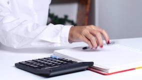 Γυναίκα με να βασιστεί σχεδιαγραμμάτων στον υπολογιστή και το γράψιμο στο σημειωματάριο κλείστε επάνω φιλμ μικρού μήκους