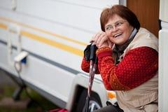 Γυναίκα με πεζοποριεις Πολωνούς καθμένος στην πόρτα τροχόσπιτων Στοκ εικόνα με δικαίωμα ελεύθερης χρήσης
