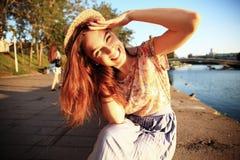 Γυναίκα με τα άσπρα δόντια που σκέφτονται και που κοιτάζουν λοξά σε ένα πάρκο το καλοκαίρι Στοκ εικόνα με δικαίωμα ελεύθερης χρήσης