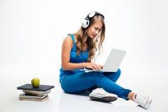 Γυναίκα με τα ακουστικά και τη χρησιμοποίηση του lap-top στο πάτωμα στοκ εικόνα