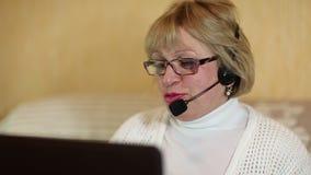 Γυναίκα με τα ακουστικά με τις συζητήσεις μικροφώνων σε έναν πελάτη μέσω του υπολογιστή απόθεμα βίντεο