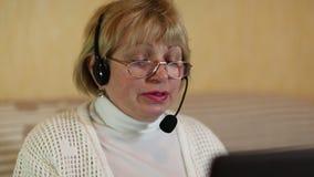 Γυναίκα με τα ακουστικά με τις συζητήσεις μικροφώνων σε έναν πελάτη μέσω του υπολογιστή φιλμ μικρού μήκους