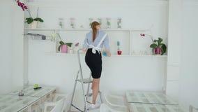 Γυναίκα με τα ακουστικά που καθαρίζουν τη σκόνη από το ράφι στο ξενοδοχείο απόθεμα βίντεο