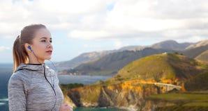 Γυναίκα με τα ακουστικά που τρέχουν πέρα από τη μεγάλη ακτή sur Στοκ Εικόνα
