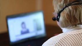 Γυναίκα με τα ακουστικά στις συζητήσεις υπολογιστών σε έναν πελάτη μέσω του υπολογιστή φιλμ μικρού μήκους