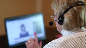 Γυναίκα με τα ακουστικά στις συζητήσεις υπολογιστών σε έναν πελάτη φιλμ μικρού μήκους