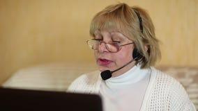 Γυναίκα με τα ακουστικά στις συζητήσεις υπολογιστών σε έναν πελάτη απόθεμα βίντεο