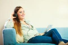 Γυναίκα με τα ακουστικά ταμπλετών που κάθεται στον καναπέ Στοκ Εικόνες