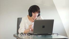Γυναίκα με τα ακουστικά με τις συζητήσεις μικροφώνων σε έναν πελάτη μέσω του υπολογιστή Η γυναίκα με το PC επικοινωνεί μέσω του s απόθεμα βίντεο