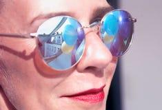 Γυναίκα με τα γυαλιά ηλίου με την αντανάκλαση των ζωηρόχρωμων μπαλονιών Στοκ Εικόνα