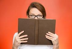 Γυναίκα με τα γυαλιά που κρύβουν το πρόσωπο πίσω από το βιβλίο στοκ εικόνες