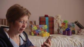 Γυναίκα με τα δώρα στο υπόβαθρο που χρησιμοποιεί το smartphone να ψωνίσει on-line απόθεμα βίντεο