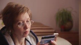 Γυναίκα με τα δώρα στο υπόβαθρο που χρησιμοποιεί το smartphone να ψωνίσει on-line με την πιστωτική κάρτα απόθεμα βίντεο
