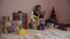 Γυναίκα με τα δώρα Χρησιμοποιώντας το smartphone να ψωνίσει on-line απόθεμα βίντεο