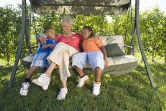 Γυναίκα με τα εγγόνια που κάθονται στην έδρα ταλάντευσης στοκ εικόνες με δικαίωμα ελεύθερης χρήσης