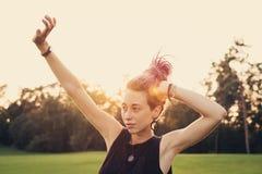 Γυναίκα με τα ζωηρόχρωμα dreadlocks που τεντώνουν και που χορεύουν υπαίθρια Στοκ Εικόνες