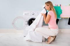 Γυναίκα με τα καθαρισμένα ενδύματα κοντά στο ηλεκτρονικό πλυντήριο Στοκ Εικόνες