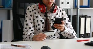 Γυναίκα με τα κόκκινα ακουστικά στους ώμους που κρατούν την πιστωτική κάρτα και που χρησιμοποιούν το smartphone απόθεμα βίντεο