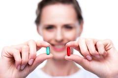 Γυναίκα με τα κόκκινα και μπλε χάπια Στοκ Εικόνα