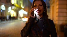 Γυναίκα με τα κόκκινα χείλια που μιλούν στο smartphone και τους περίπατους κατά μήκος της μεσαιωνικής οδού απόθεμα βίντεο