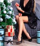 Γυναίκα με τα μακριά πόδια που κάθεται από το χριστουγεννιάτικο δέντρο στοκ εικόνες