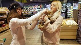 Γυναίκα με τα μπισκότα αγοράς κορών στην υπεραγορά απόθεμα βίντεο