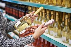 Γυναίκα με τα μπουκάλια του τριαντάφυλλου και του άσπρου κρασιού στο κατάστημα στοκ εικόνες