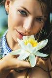 Γυναίκα με τα μπλε μάτια με τον άσπρο κρίνο νερού υπό εξέταση Στοκ φωτογραφία με δικαίωμα ελεύθερης χρήσης