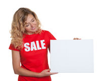 Γυναίκα με τα ξανθά μαλλιά σε ένα πουκάμισο πώλησης που παρουσιάζει σε μια πινακίδα στοκ φωτογραφίες με δικαίωμα ελεύθερης χρήσης