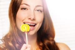 Γυναίκα με τα οδοντικά στηρίγματα που δαγκώνουν μακριά το στρόβιλο lollipop Στοκ εικόνα με δικαίωμα ελεύθερης χρήσης