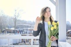 Γυναίκα με τα λουλούδια κοντά στην ακροθαλασσιά στοκ φωτογραφίες