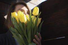 Γυναίκα με τα λουλούδια σε ένα σκοτεινό δωμάτιο στοκ εικόνες