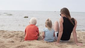 Γυναίκα με τα παιδιά που κάθονται στην παραλία απόθεμα βίντεο