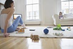 Γυναίκα με τα παιχνίδια στο πάτωμα ενώ κόρη στον καναπέ στοκ φωτογραφίες