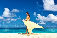 Γυναίκα με τα σαρόγκ στην παραλία Στοκ Φωτογραφία